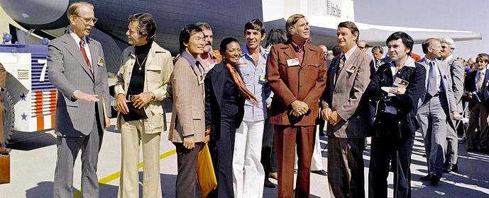 Certain members of the Star Trek cast and creators stand in front of the Shuttle Enterprise